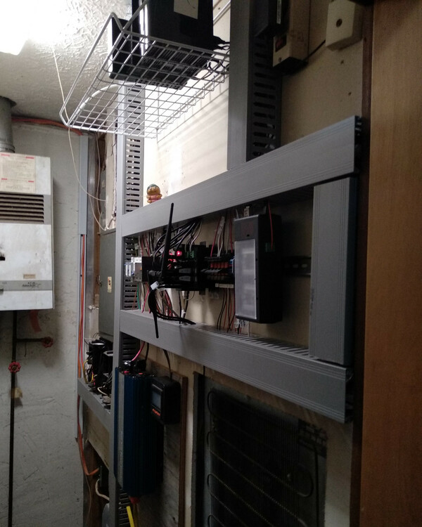 A cramped utility room with an entire wallcovered with electronic gear, including the DIN rail, which is surrounded bywire gutters