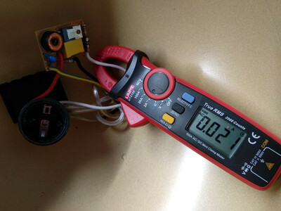 clamp multimeter reading 0.02 amps AC, connected to a small circuit board with a yellow capacitor, a coil, and a heat sinked IC visible