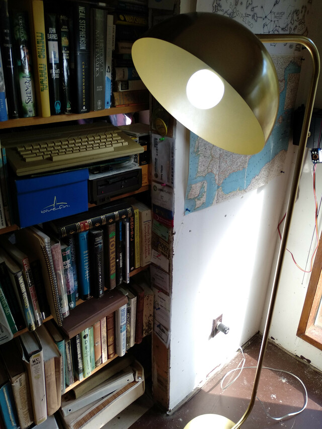 front view of lit lamp beside a bookcase