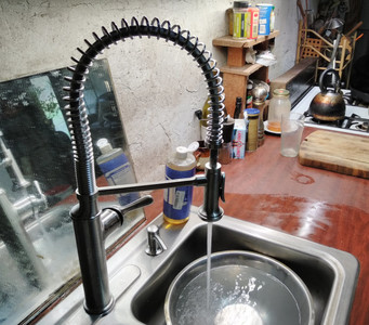 modern restaurant-style sprung arched faucet with water flowing into the kitchen sink