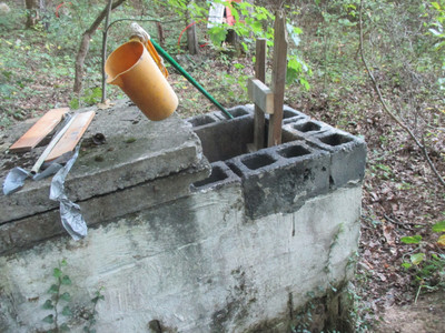 very narrow concrete water tank with its concrete lid opened and a rough wooden ladder sticking out of it