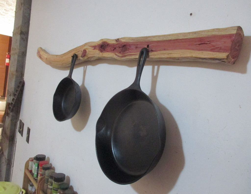slightly curved wood beam with cast iron pots hung from it