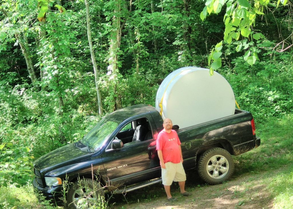 Joey standing in front of a black 4x4 pickup truck with a large white 550 gallon water tank on its side in the bed and arching high above